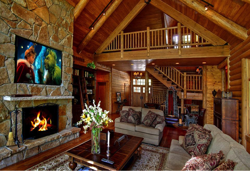 luxury log home with tv above fireplace