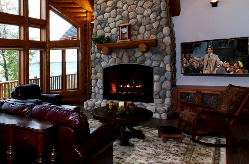 luxury log home with tv next to fireplace